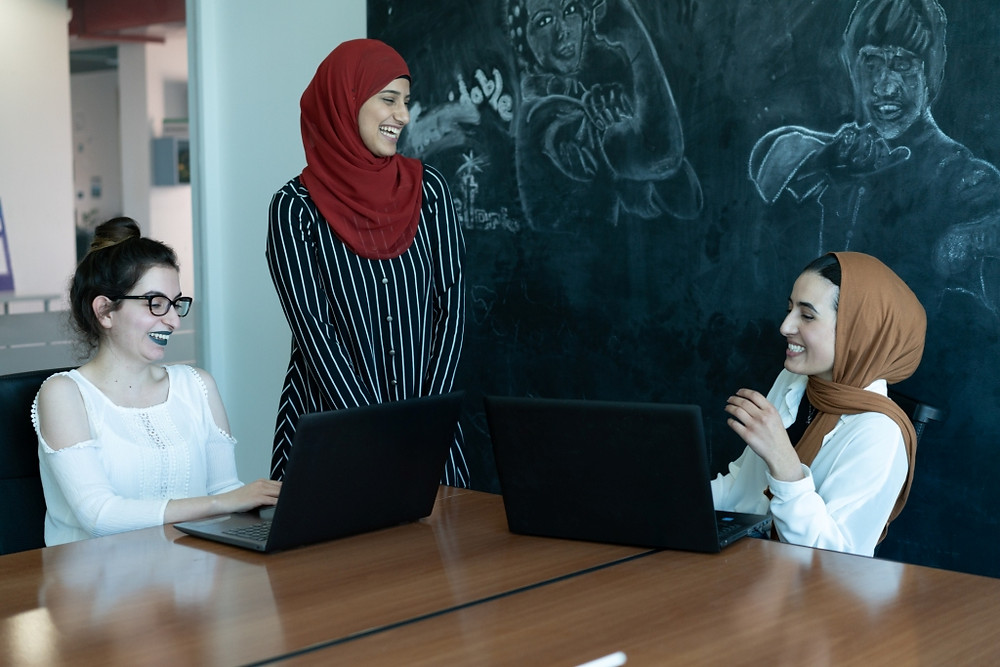 Three women in an office, two wearing hijab