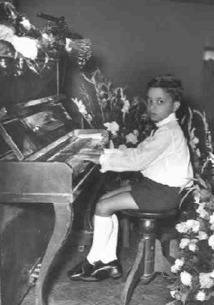 Jasnam as a child playing the piano