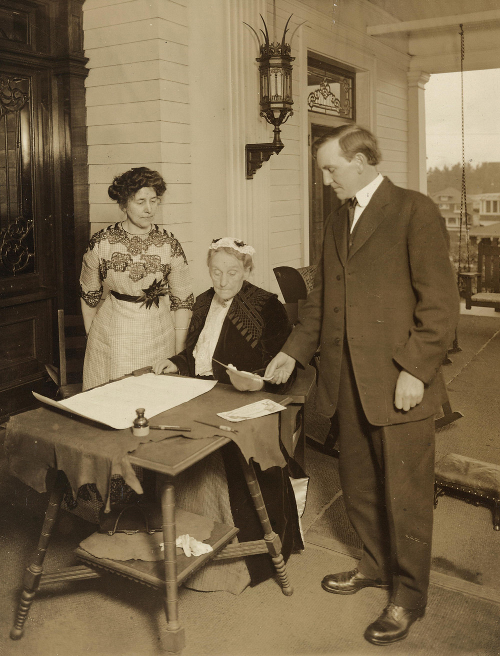 Abigail Scott Duniway signing first Equal Suffrage Proclamation ever made by a woman. Governor Oswald West, who had signed the Proclamation is shown looking on, and acting President Dr. Viola M. Coe is standing near.