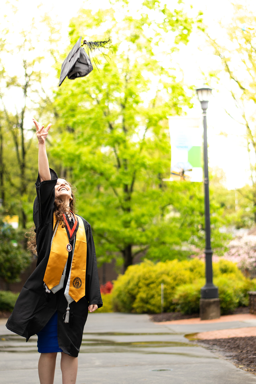 Woman throwing mortarboard in air