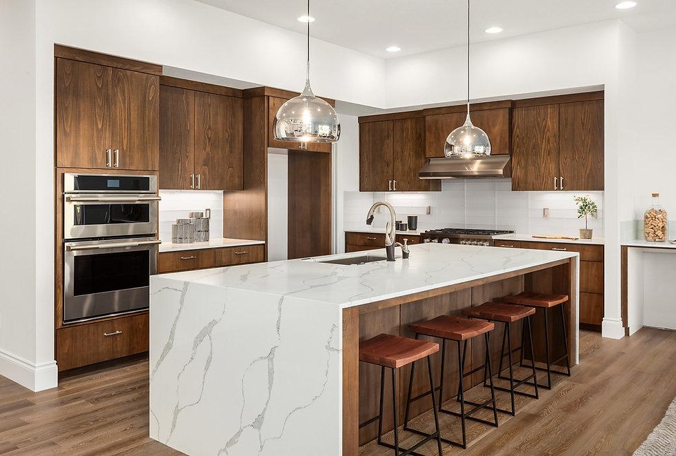 Kitchen in new luxury home with quartz waterfall island, hardwood floors, dark wood cabine