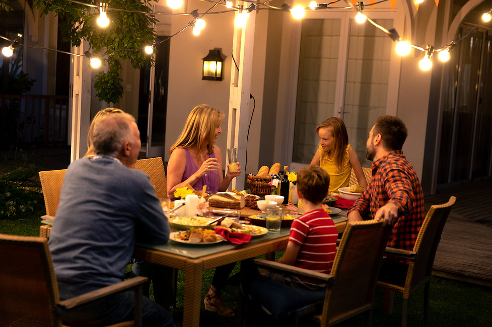 Side view of a multi-generation Caucasian family sitting outside at a dinner table in the
