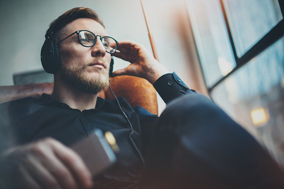 Portrait handsome bearded man wearing glasses,headphones listening to music at modern home...und.jpg
