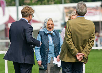 Her majesty the Queen laughing heartily after being presented with a Tesco gift voucher for the victory of one of her horse at Royal Windsor Horse Show.