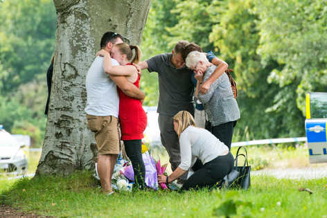 Scene where a knifeman in his 30s stabbed a 79-year-old motorist to death in a suspected road rage attack after the pensioner crashed into the back of his car. Picture shows wife Maureen Lock and family laying flower at the murder scene.