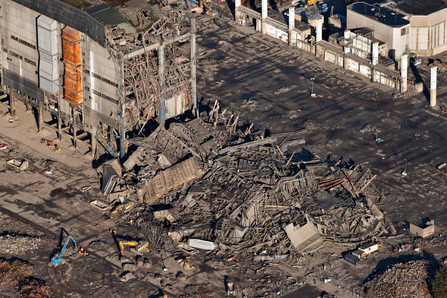 Rescuers wearing orange coloured reflective overalls clamber over the twisted metal and rubble where it is feared three men are buried following the collapse of a building awaiting demolition at Didcot B Power Station in Oxfordshire.