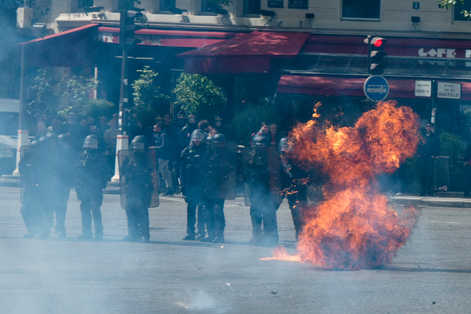 Riot police being attack with molotov cocktail at May 1st riots in Paris.