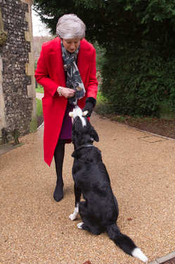 PM Theresa May attends Christmas morning Sunday service at St Andrew's church in Sonning, Berks. Picture shows PM giving Blitz the dog a xmas present.