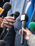 Press microphones pointed at a person in a suit