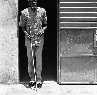 Seeing impaired man, standing in front of a building, holding a walking stick.