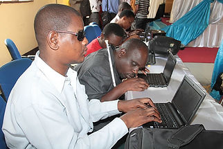 Seeing impaired men working with computers in a computer lab.
