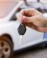 Male holding car keys with car on backgr