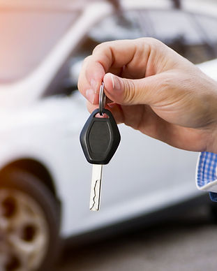 Male holding car keys with car on backgr