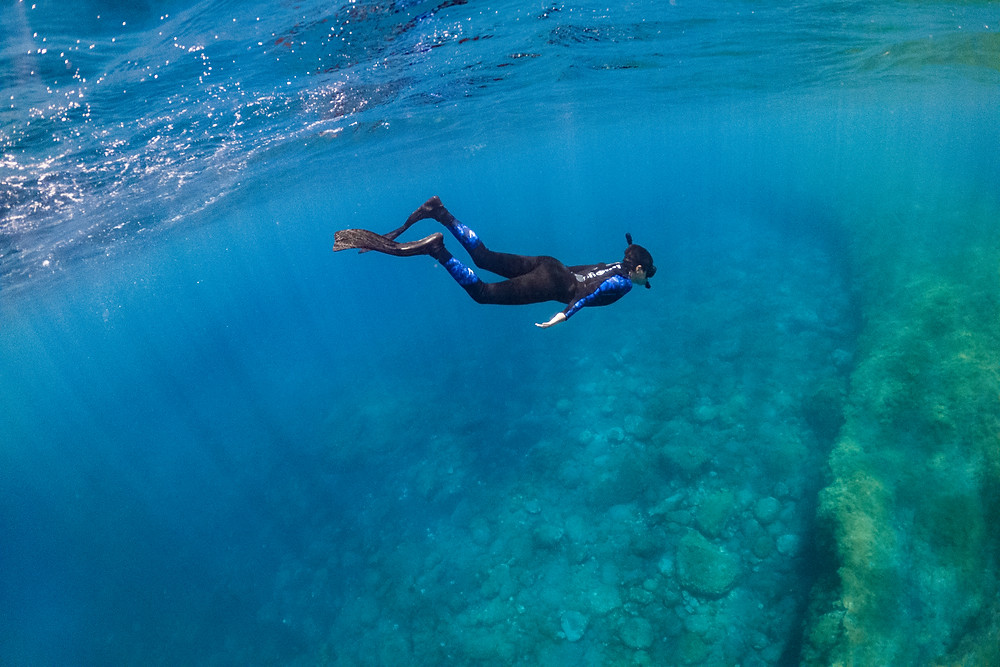 A snorkeler is diving down and watching a dramatic underwater landscape.