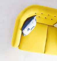 Modern couch in a yellow fabric with blue tufted buttons on the back and a nautical-themed throw pillow