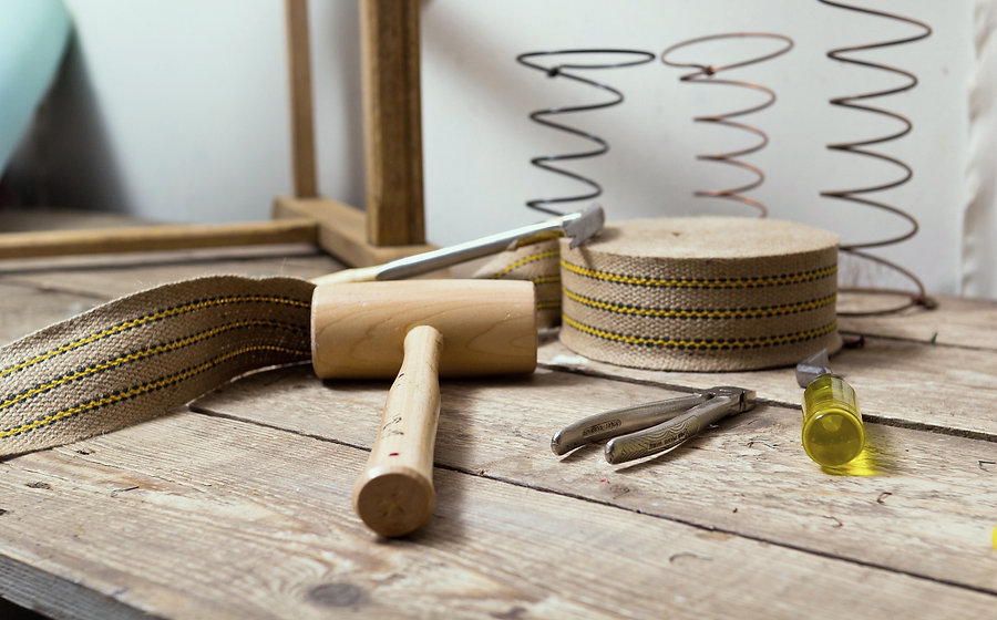 Traditional upholstery supplies and tools laid on an upholsterer's work bench