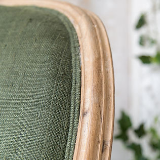 Close up of vintage chair with green upholstery and double welt cord