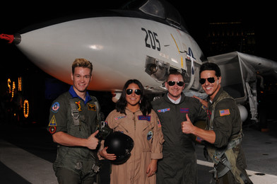 Two party-goers pose with a Tom Cruise lookalike on the flight deck of the USS Midway Museum