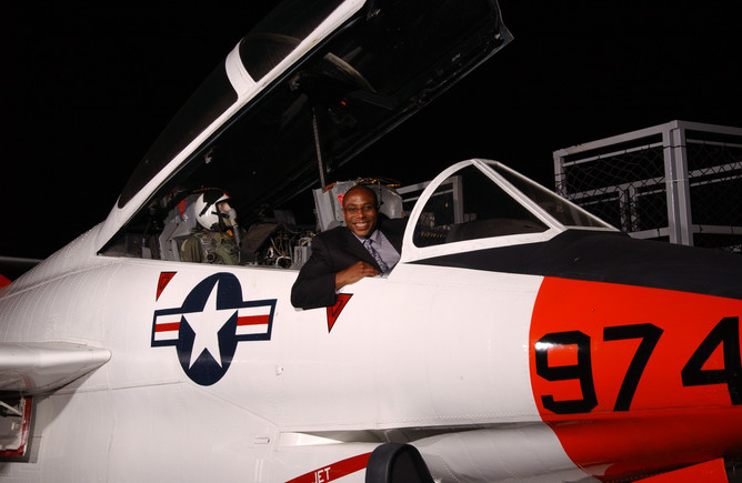 A man sits inside a jet on the flight deck of the USS Midway