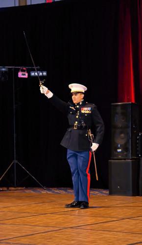 The adjutant raises his saber at his post.