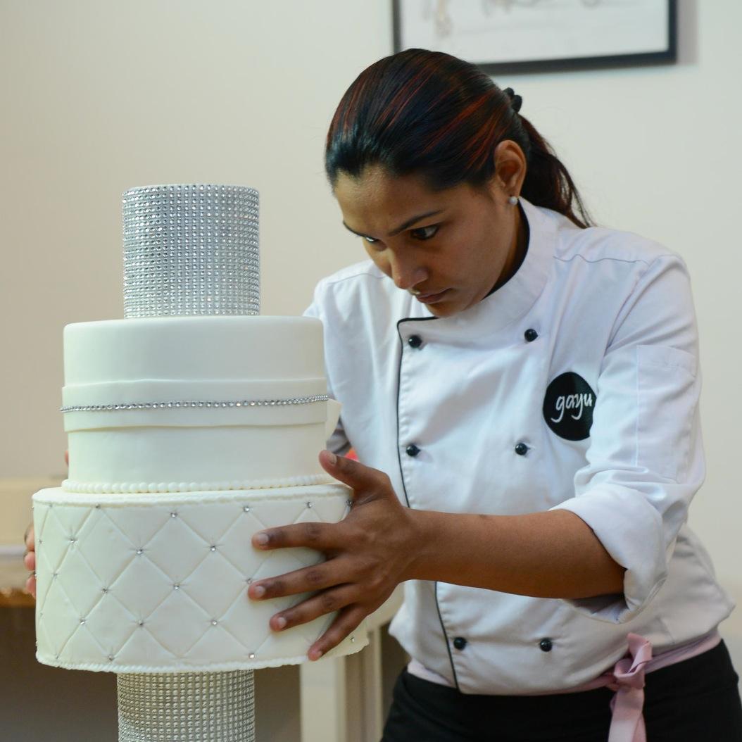 Chef gayu stacking a wedding cake