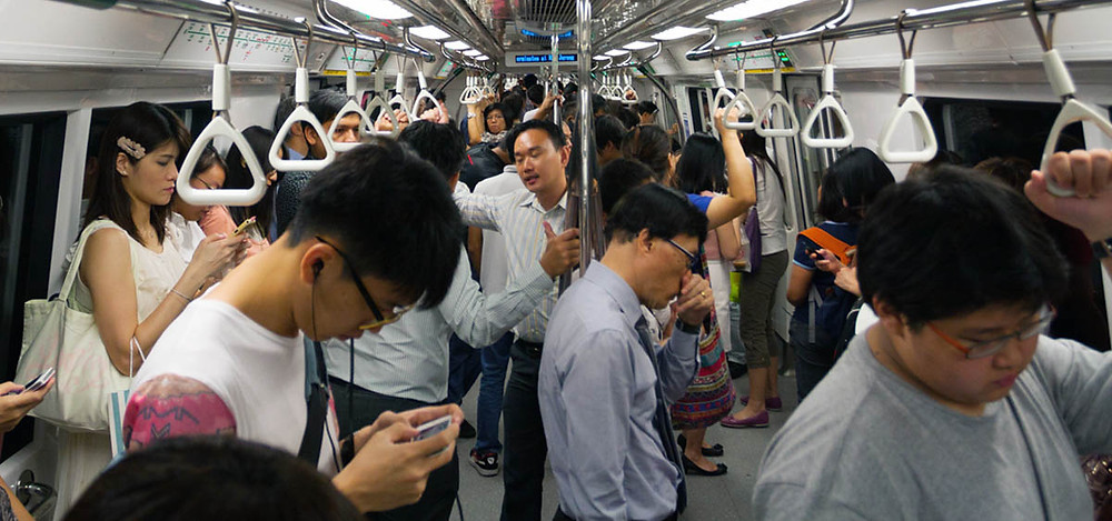 mrt train people standing looking down at phones