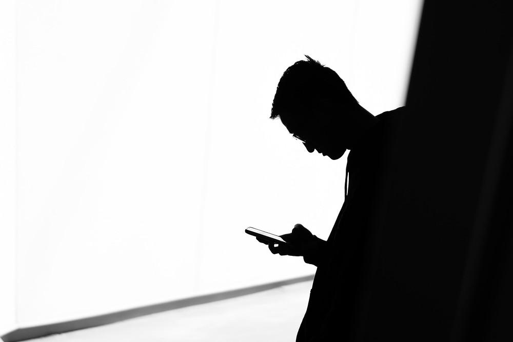 man looking down on phone fhp forward head posture