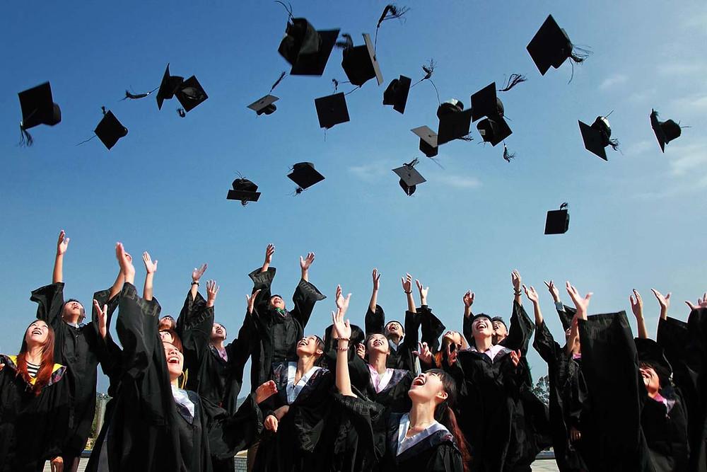 Graduates throwing hats into sky | Align Chiropractic
