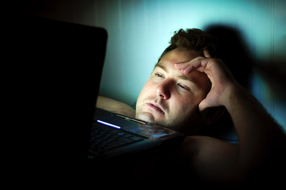 Man laying in bed using laptop in bad posture