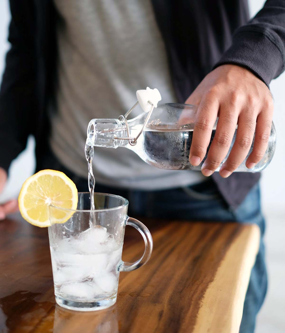 Man pouring water into a glass with lemon slice