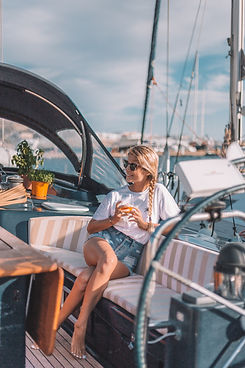"<img src=""deck of a sailing boat.png"" alt=""A girl is drinking a glass of wine on the deck of a sailing boat"">"