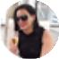 Mulher branca com cabelos pretos camisa preta com óculos pretos segurando taça de vinho