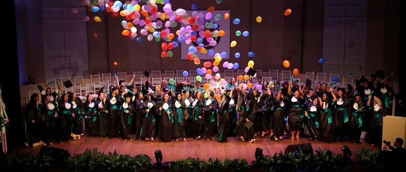 Vários alunos em cima de um palco vestidos com becas alegres com vários balões sobre eles