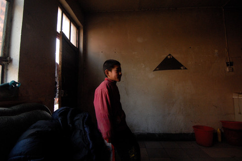 The boy from next door watches the fun as three guys from Yunnan get up mid-morning – the first thing that they do is strike up the fire and start warming up for a bit of karaoke.