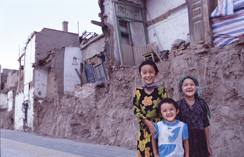 "In May 2002, I was walking along a new boulevard that cut a clean concrete line through inner-city Kashgar when three girls popped up, smiling. With fingers making circles around their eyes, they indicated that they wanted their photograph taken.   ""Okay,"" I said, mainly fixated by the interface between what was to be retained of the existing dwellings and what had to give way to the road. I asked them to stand on the earth embankment that started as soon as the new footpath ended.  Without prompting, the girls pointed and the older one said in Mandarin ""we live there."" They were pointing to the remains of a room less than 2 metres wide and completely open on one side except for some red, white, and blue tarpaulin. Surely they meant the rooms behind? ""No"" they replied."