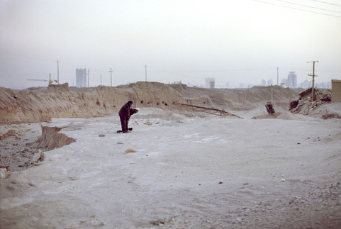 Uyghur Muslims offering the afternoon prayer. The squatter-periphery of Korla, late 2007. Just visible (left) through the haze behind them, on the city skyline, is the head office building of the Tarim Oilfield Company.