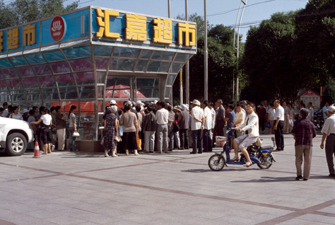 July 10, 2009. Supermarkets in Korla open for the first time since the July 5 violence in Urumqi. Usually they open at 9:30 AM or 10 AM, but the tension and fear had shortened trading hours: this one was due to open at 11 AM. Despite the word on the street being to stay away from public and crowded places, it seemed to me that these people found solace in the familiar jostle. The very image of a supermarket is comfort, safety, homeliness; an antidote to the harsh rhetoric of the media and the creeping veracity of rumour.
