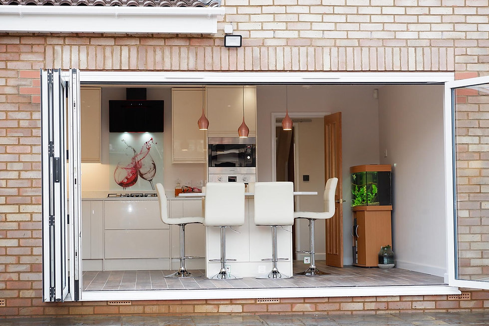 view of renovated kitchen with stylish white cabinets and bar stools, fish tank in backgro