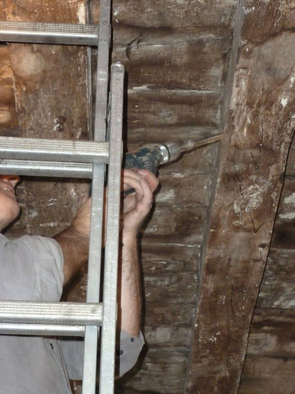 Robert drilling into the ceiling joists