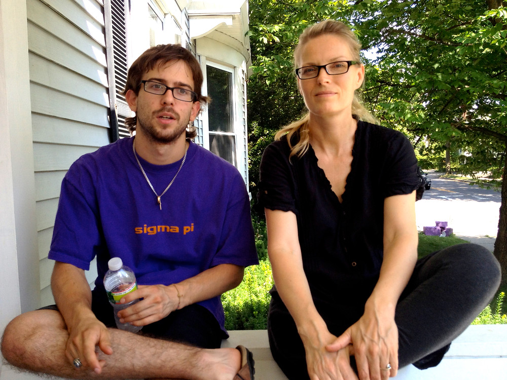 """Image if David Magnano who wearing a purple t-shirt that says """"sigma pi"""" sitting next to director Elle Kamihira, wearing black. Both are looking at the camera."""