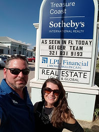 The Geiger Team standing in front of their message on the Treasure Coast Sotheby's sign