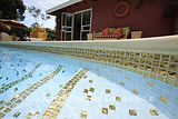 American made Lightstreams Glass Tile Renaissance Absolute White all glass tile pool with 24k gold accent pool tile and on the pool waterline.