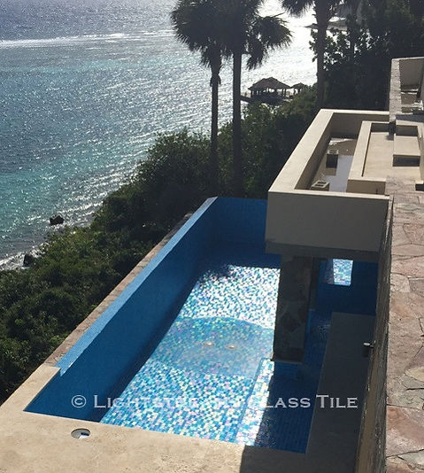 American Made Lightstreams Glass Tile Aqua Blue tile is used as pool tile and spa tile for this all glass tile pool. This photo shows the iridescent tile coloring of Lightstreams reversible tile