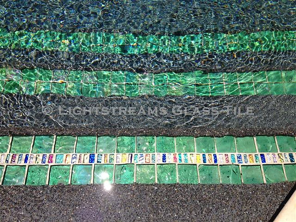 American Made Lightstreams Glass Tile, Strands of Jewel Inlays are bordered by Renaissance Collection Celadon glass green tile to create a lovely pool step marker for this swimming pool also usd for accent tile, pool tile, spa tile, floor tile, waterline tile, fountain tile, wall tile, step marker tile, kitchen tile, backsplash tile, bathroom tile, and countertop tile