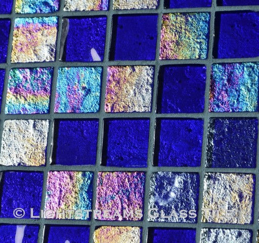 High quality American Made Lightstreams Glass Tile Renaissance Collection II Royal Blue 2.0 glass tiles are a deep royal blue on one side, with vivid rainbow iridescent colors on the reverse textured side. This blue tile can also be used for pool tile, spa tile, fountain tile, fire pit tile, wall tile, waterline tile, step marker tile, exterior tile, interior tile, accent tile, iridescent tile, backsplash tile, kitchen tile, bathroom tile, floor tile, and shower tile