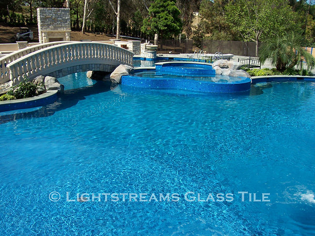 American Made Lightstreams Glass Tile Turquoise is used as pool tile, spa tile, waterline tile, bathroom tile, shower tile, and step marker blue tile with accent tile displayed around the spa around to add a stunning decorative look