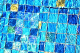 American made Lightstreams Glass Tile all glass tile pool in a mix of blue tile with 24k gold accent tile pool and spa tile