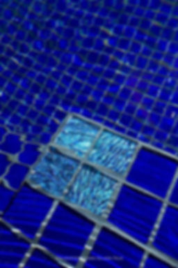 An all glass tile swimming pool of Lightstreams Renaissance Collection Royal Blue glass tiles, four Aegean Sea Jewel Glass Accent tiles create stunning medallions for the corners of the pool steps, resulting in beautiful and functional pool step markers. American Made Lightstreams Glass Tile Jewel Blue Tile which can be used as accent tile for pool tile, spa tile, waterline tile, floor tile, wall tile, step glass tile, step markers, fountain tile, kitchen tile, backsplash tile, shower tile, bathroom tile, and spillway tile