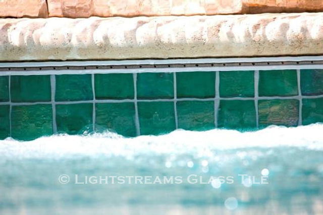 American Made Lightstreams Glass Tile Renaissance Collection Celadon green tile is used on the waterline of this pool as pool tile, step marker tile, spa tile, and waterline tile.