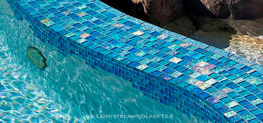 """American Made Lightstreams Glass Tile ,Pool Tile Waterline view of Mystic Spring Jewel 2""""x6"""" bullnoseglass trim tiles edging a Lightstreams Glass Tiled pool spillway ledge for iridescent accent tile"""